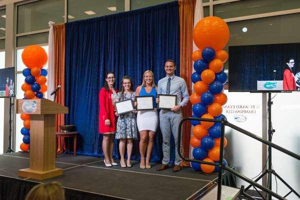 Dr. Kim Dunleavy presenting Grace Kupiszewski, erin Ginn and Brett Zebelian the Scholastic Achievement Award.