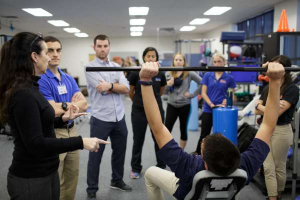 Professor explaining an exercise to a group of DPT students