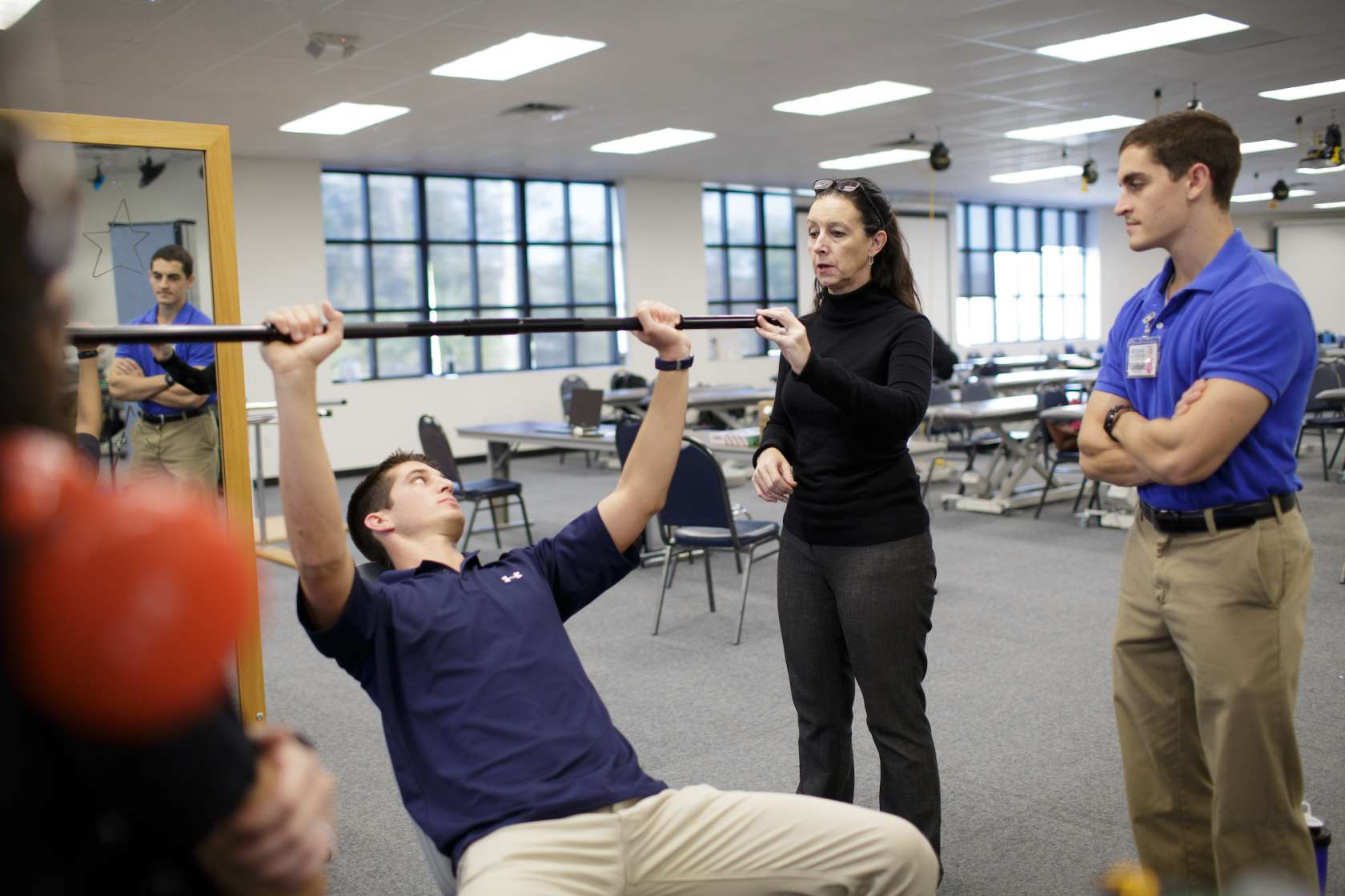 Musculoskeletal patient day, where Dr. Kim Dunleavy is explaining an exercise on a student lifting a barbell.