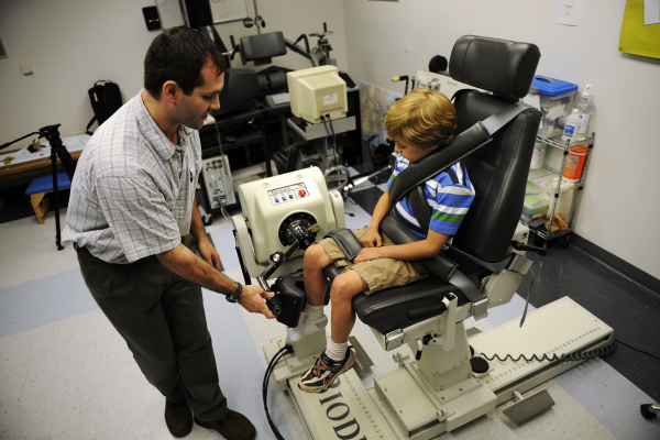 Dale Ginder, 8,  who suffers from Duchenne muscular dystrophy is tested by Donovan Lott, Ph.D., a research assistant professor in the department of physical therapy, on a Biodex machine in Gainesville, Fla., on Friday, May 14, 2010. Duchenne muscular dystrophy is an inherited disorder that involves rapidly-worsening muscle weakness and leads to increased disability. The disease currently has no cure. / Photo by Casey Brooke Lawson